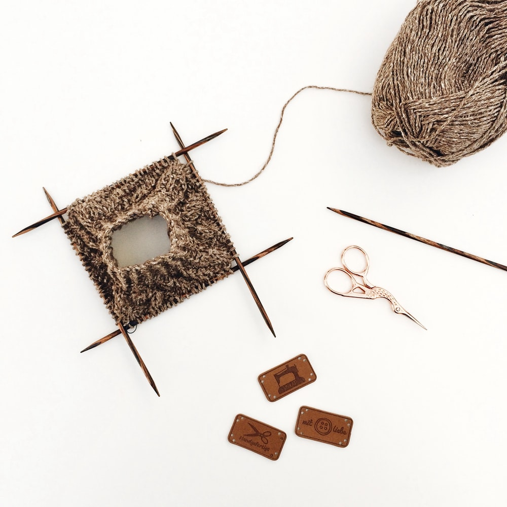 brown wooden cross and brown yarn
