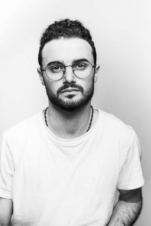 man in white crew neck shirt wearing black framed eyeglasses