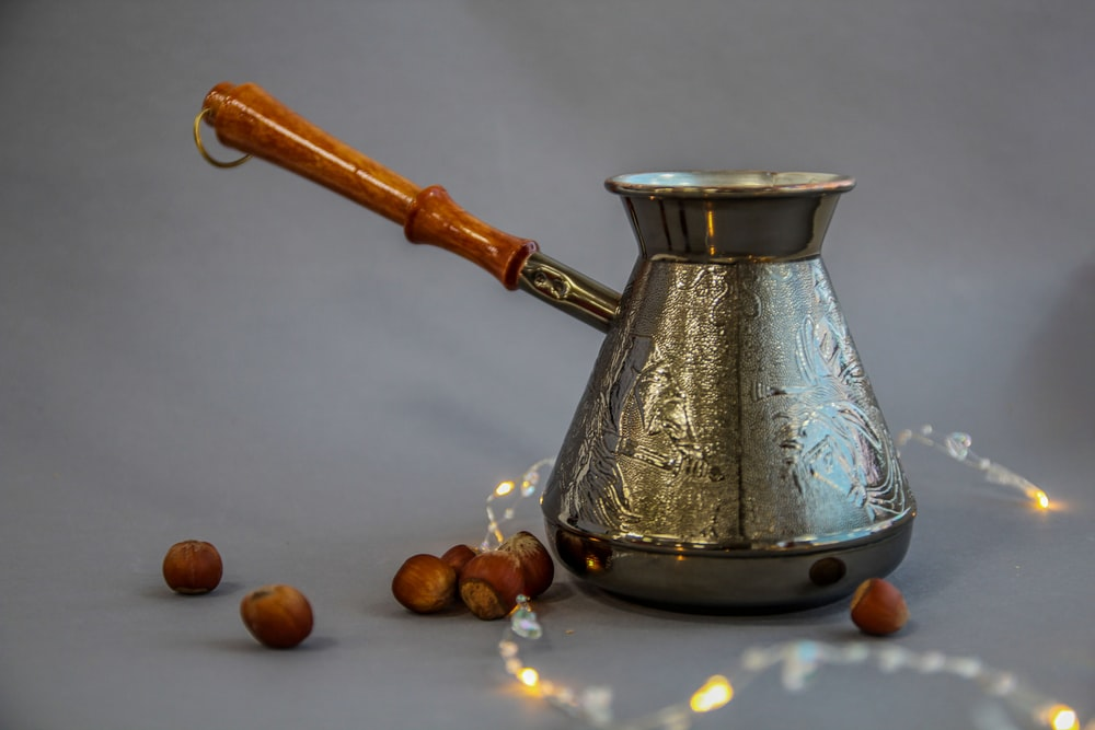 stainless steel teapot on brown round fruit