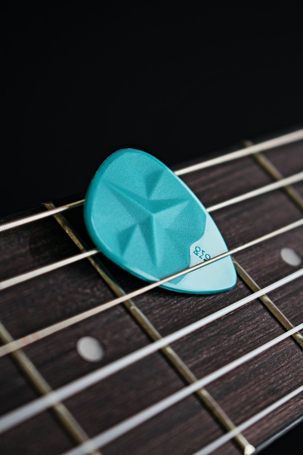 blue guitar pick on brown guitar