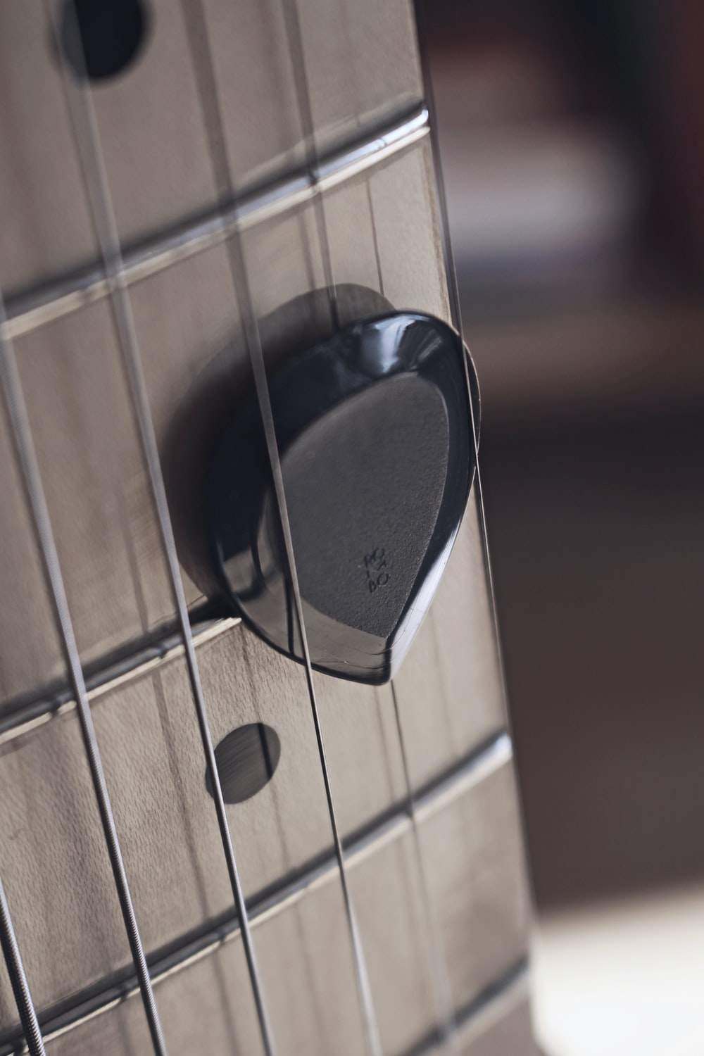 brown guitar pick in close up photography