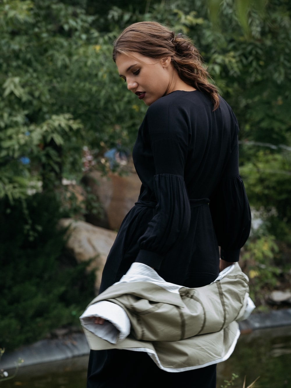 woman in black long sleeve shirt and white pants sitting on concrete bench during daytime