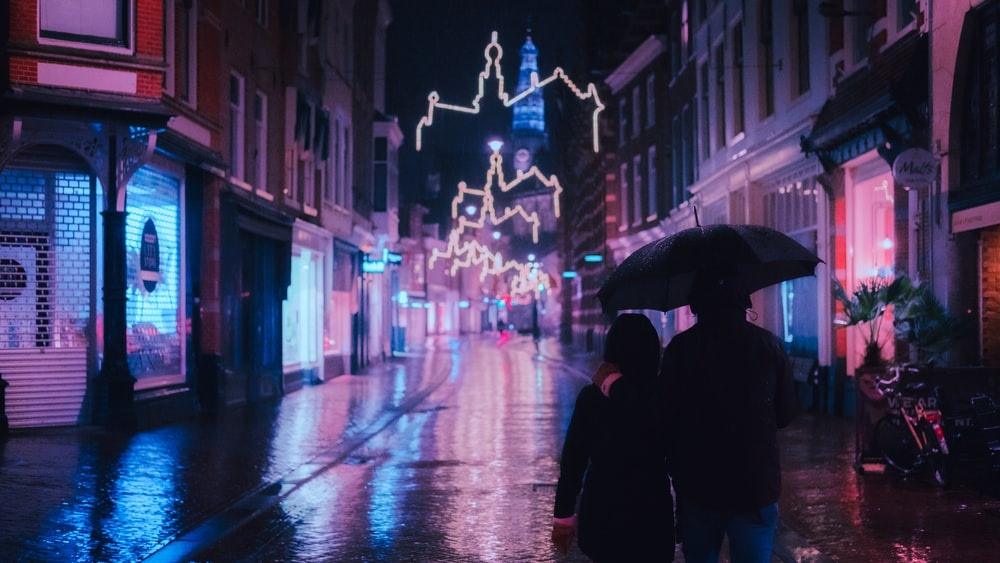 person in black coat holding umbrella walking on street during night time