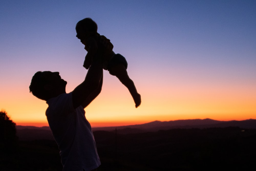 silhouette of man and woman kissing during sunset