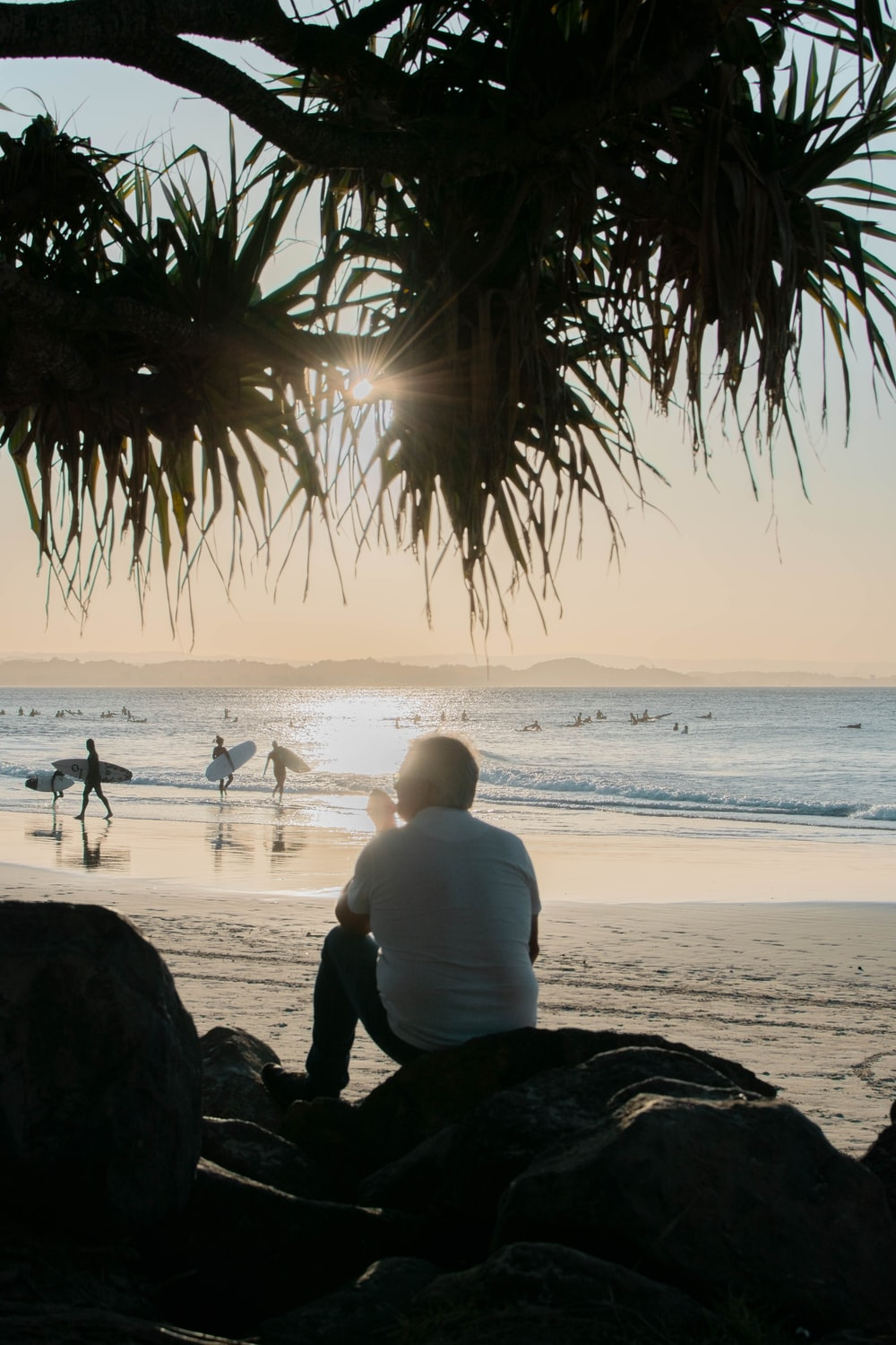 man in white shirt sitting on beach shore during sunset