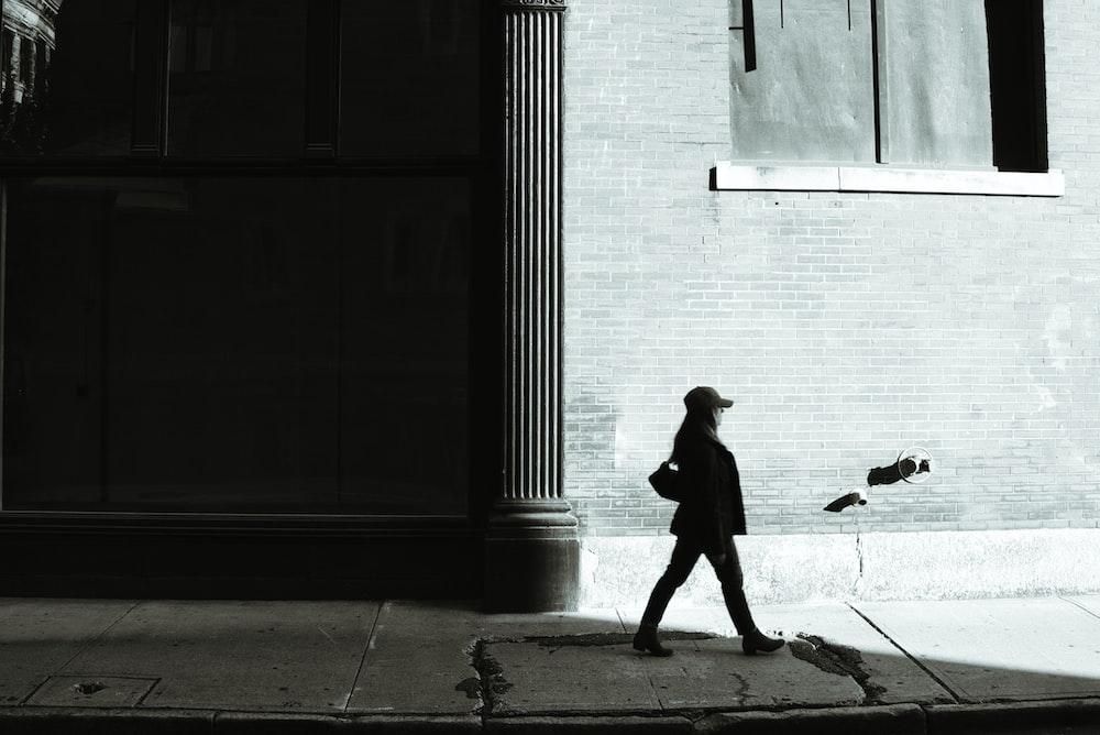 man walking on sidewalk near building