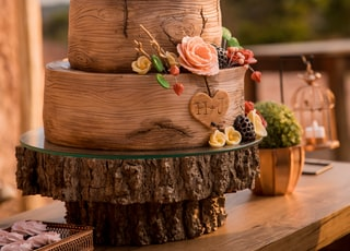 brown and pink floral cake on brown wooden round table