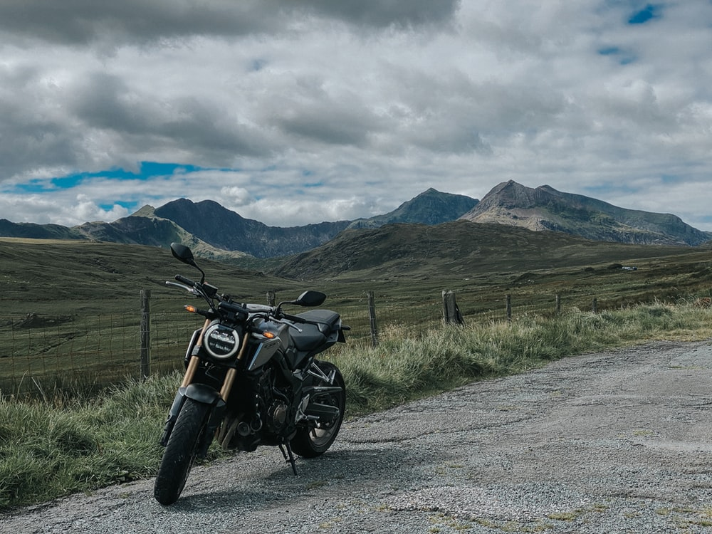 black motorcycle parked on gray asphalt road near green grass field and mountain under white clouds