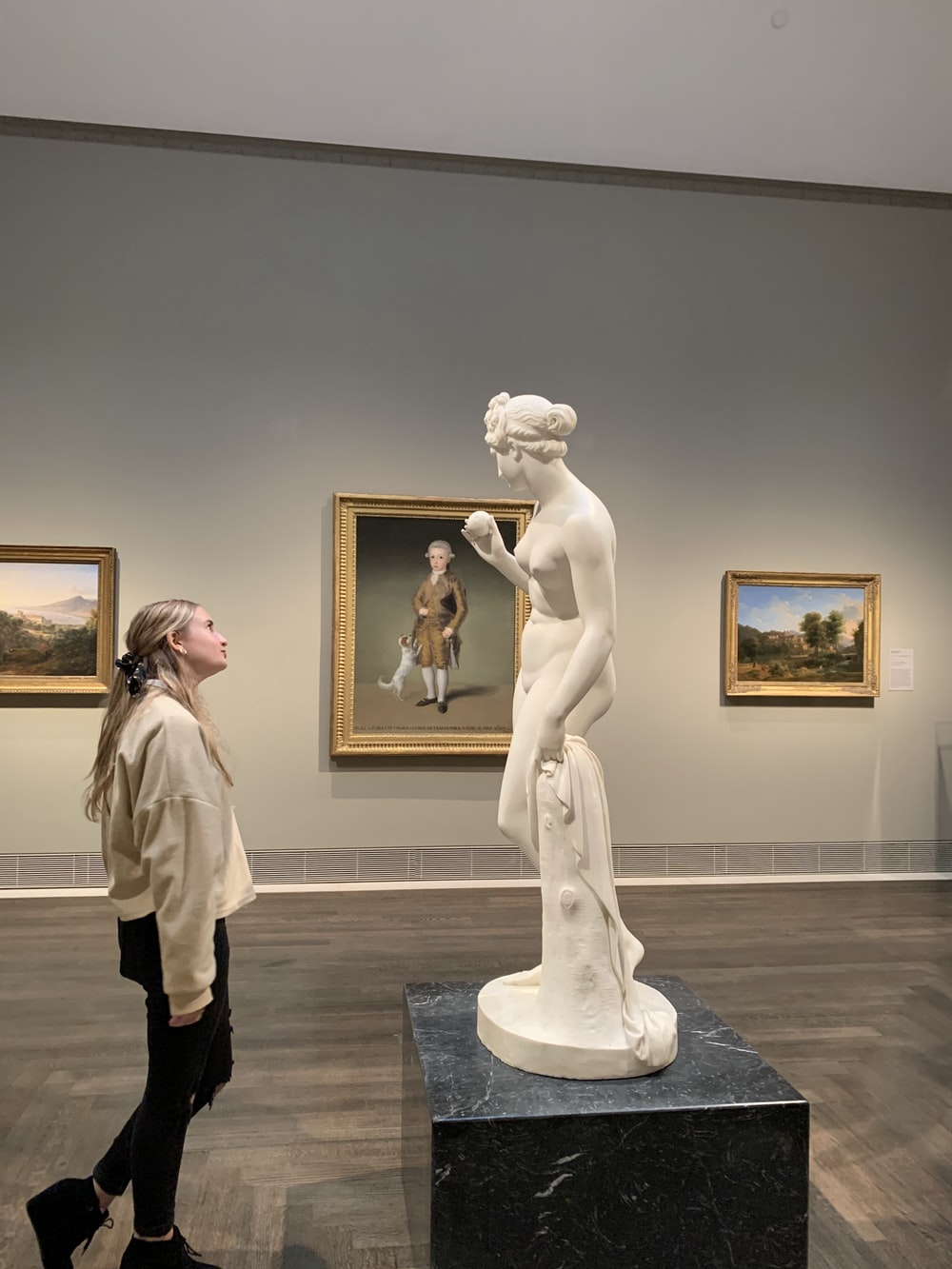 woman in beige coat standing near white statue