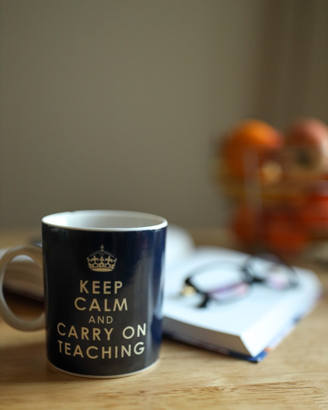 A mug stating 'Keep Calm and Carry on Teaching' in front of a diary and glasses