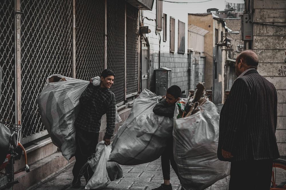 man in black jacket and gray pants holding black plastic bag
