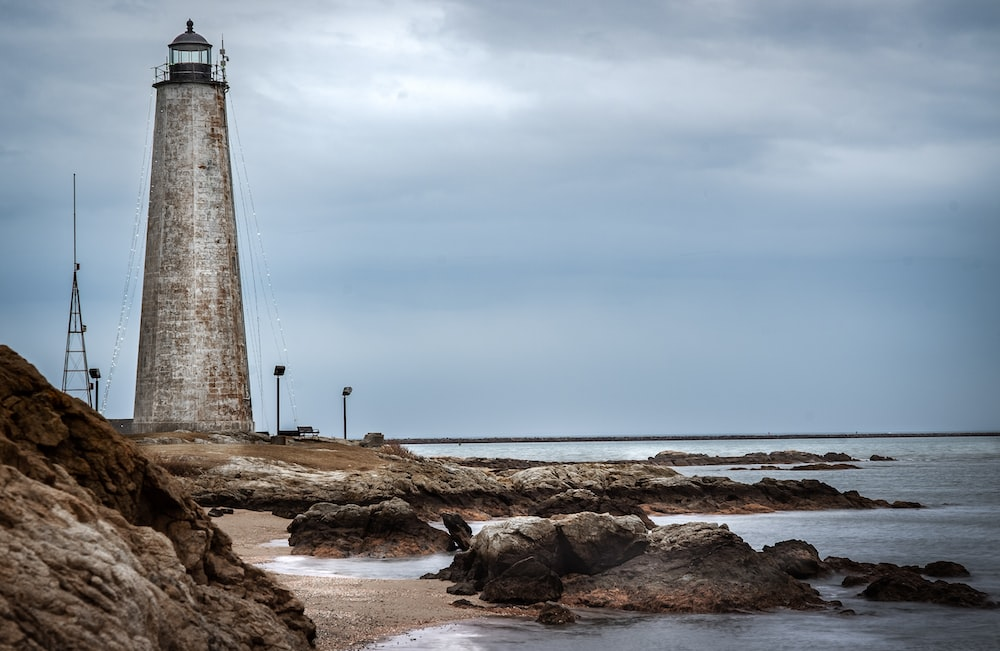 white and black lighthouse on brown rocky shore under blue sky during daytime