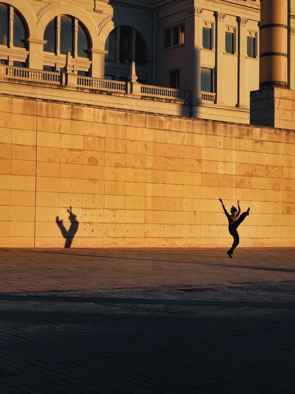 man in black jacket and pants jumping near beige concrete building during daytime