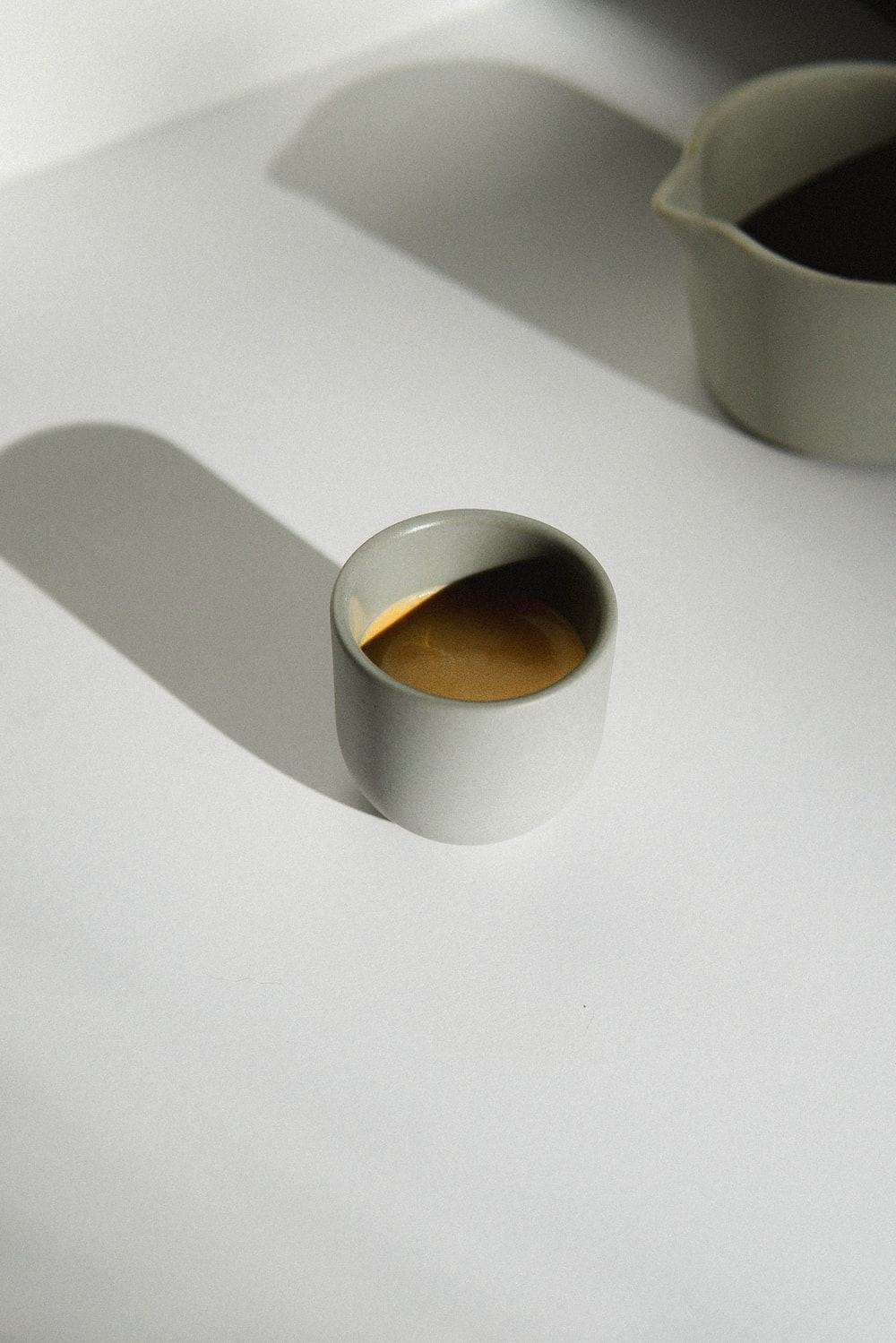 white ceramic mug with brown liquid
