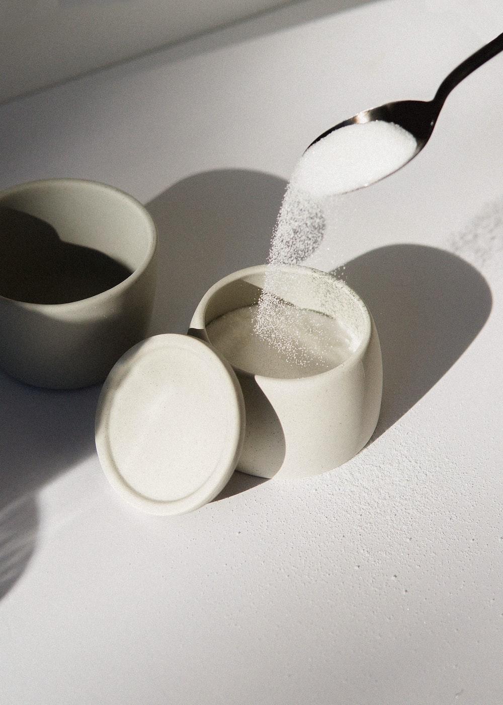 white ceramic mugs on white table