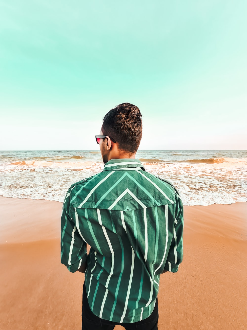 man in green and white stripe shirt standing on beach during daytime