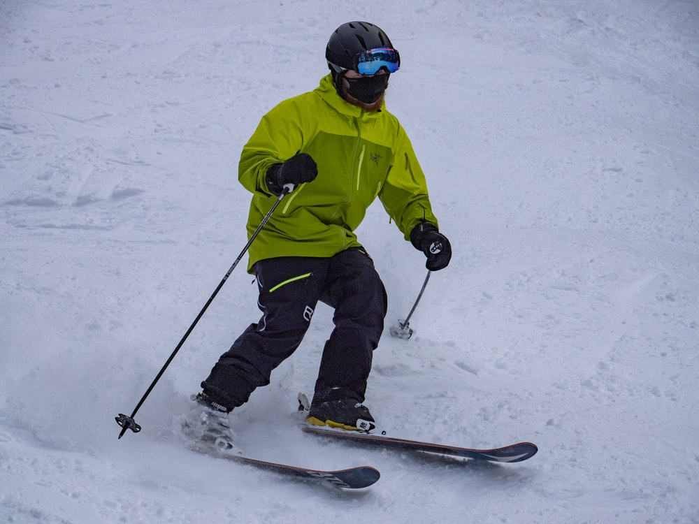 person in green jacket and black pants riding on snowboard