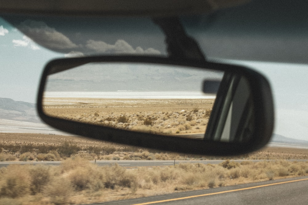 black car side mirror reflecting brown field during daytime