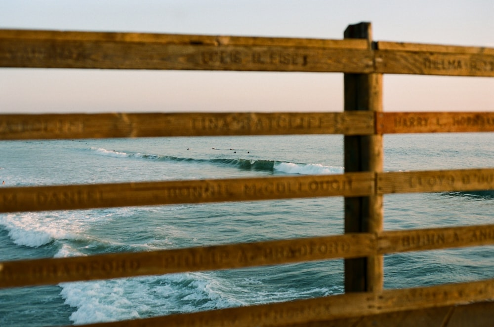 brown wooden fence on body of water during daytime