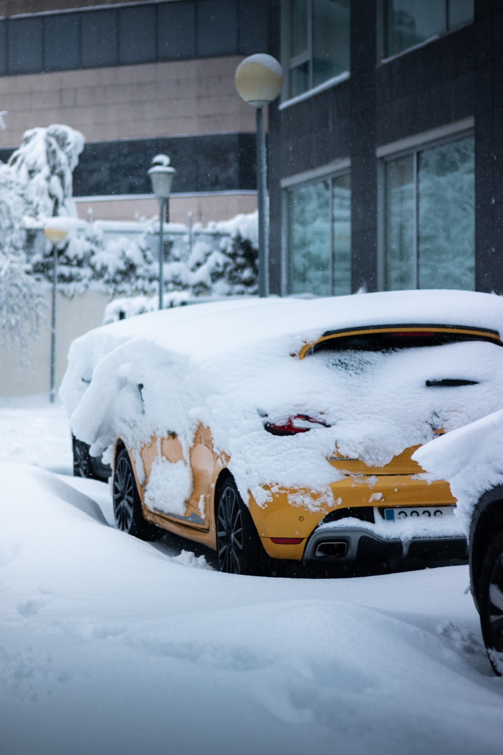 yellow car covered with snow