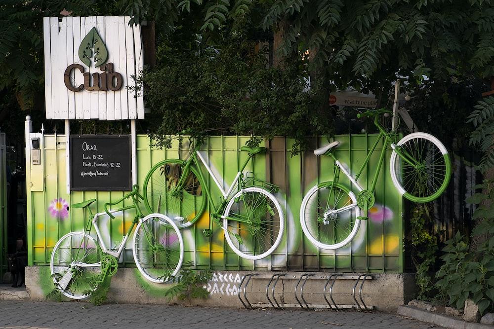 green city bike parked beside green plants