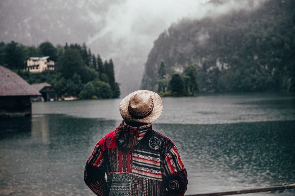 person in red black and white plaid shirt wearing brown straw hat standing near body of with with with with