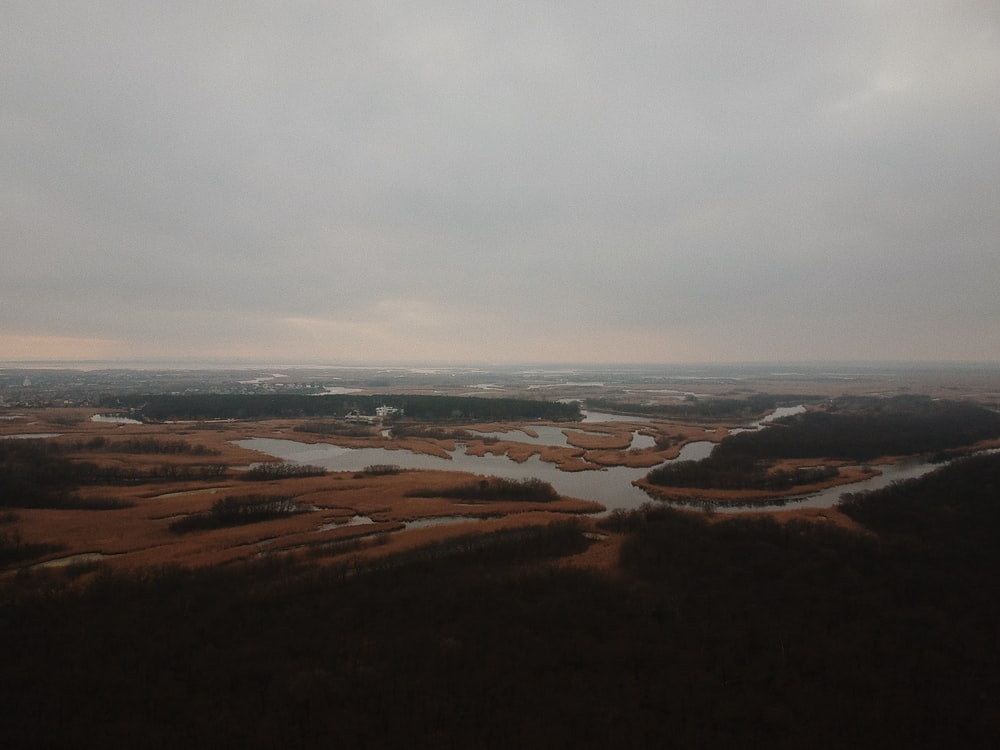 aerial view of brown field under cloudy sky during daytime