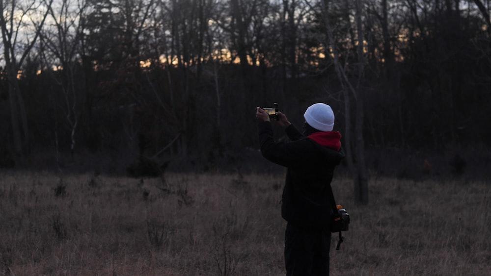 man in black jacket holding camera taking photo of trees during daytime