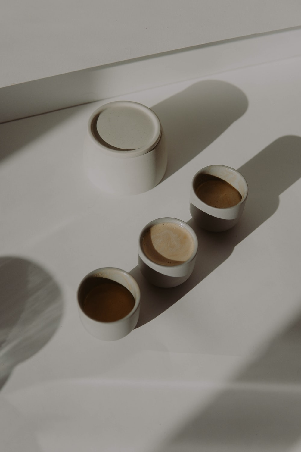 3 white ceramic cups on white table