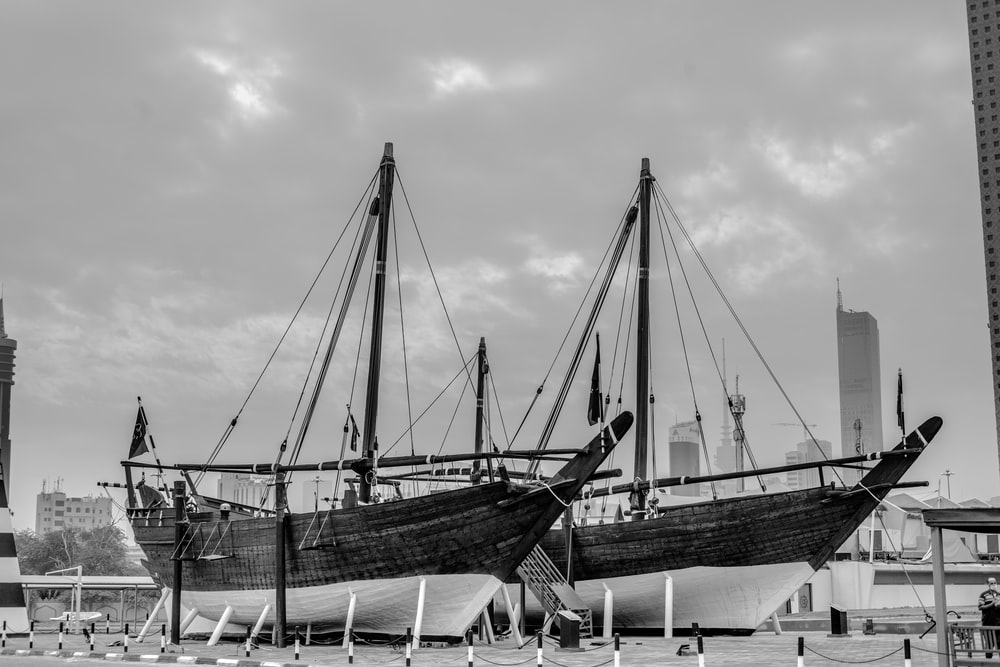 grayscale photo of boat on dock