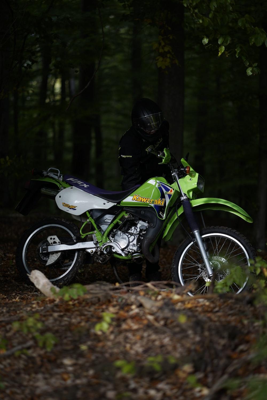 man riding white and green motocross dirt bike