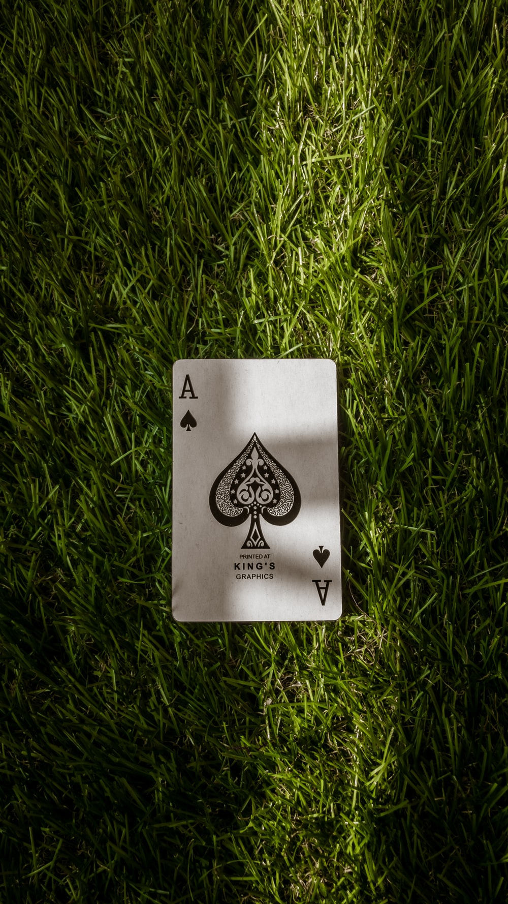 ace of spade playing card on green grass