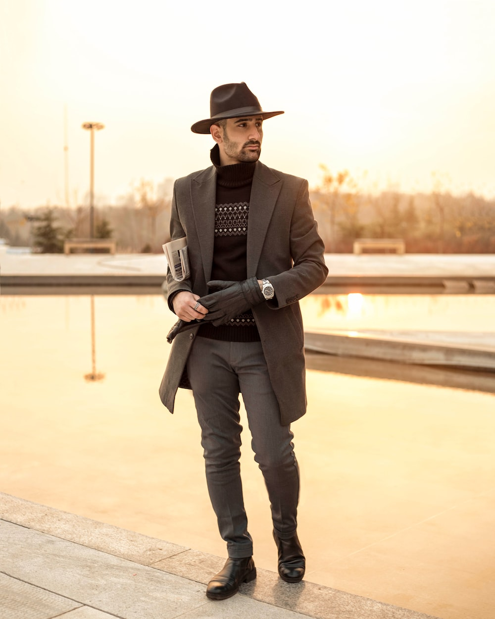 man in black blazer and gray pants wearing black fedora hat standing on gray concrete pavement