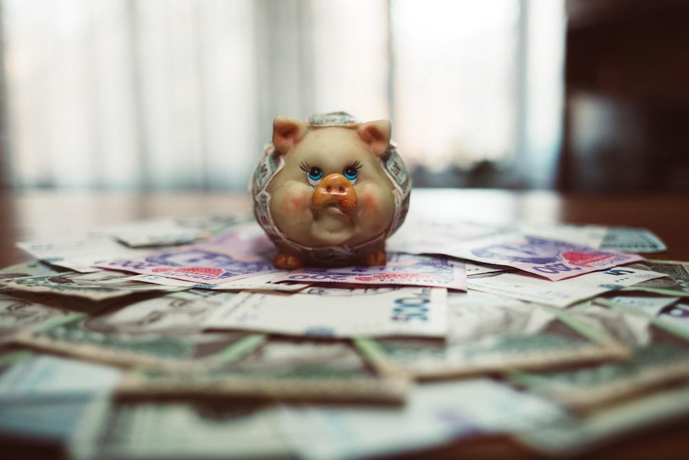 pink pig ceramic figurine on white newspaper