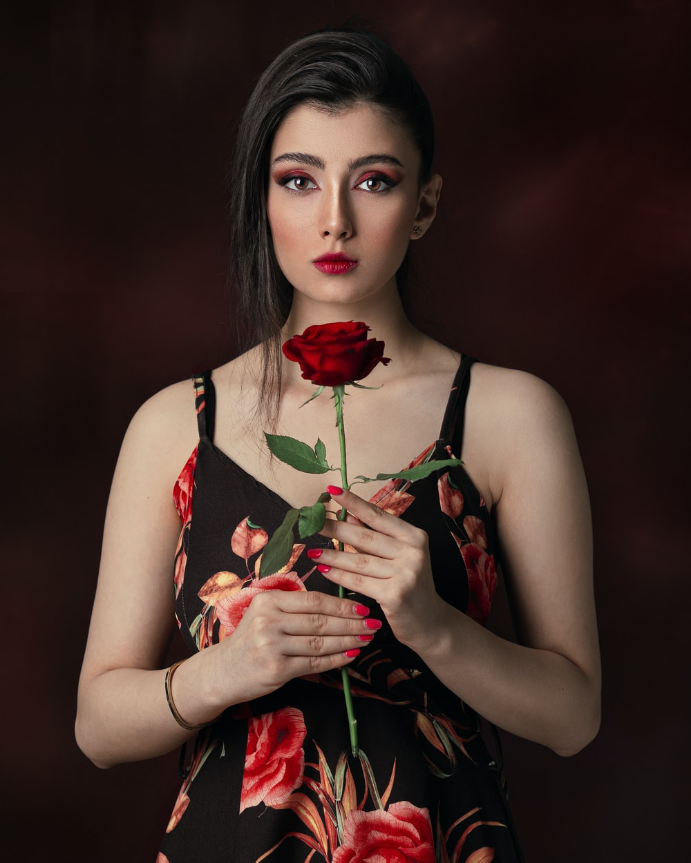 woman in black and red floral tank top holding red rose