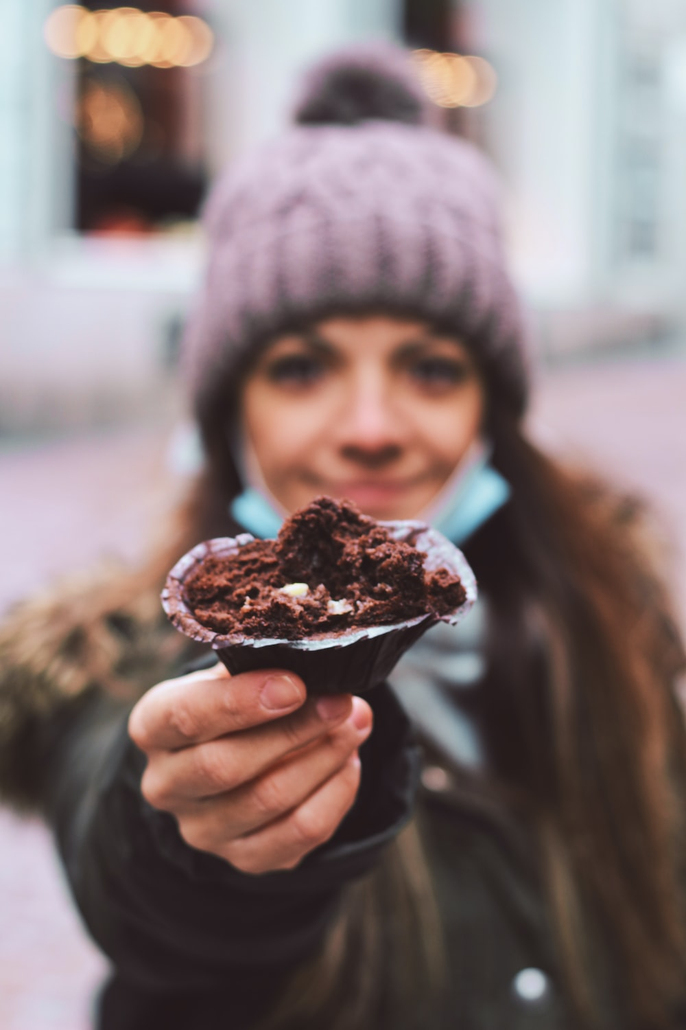 person in black knit cap holding chocolate ice cream