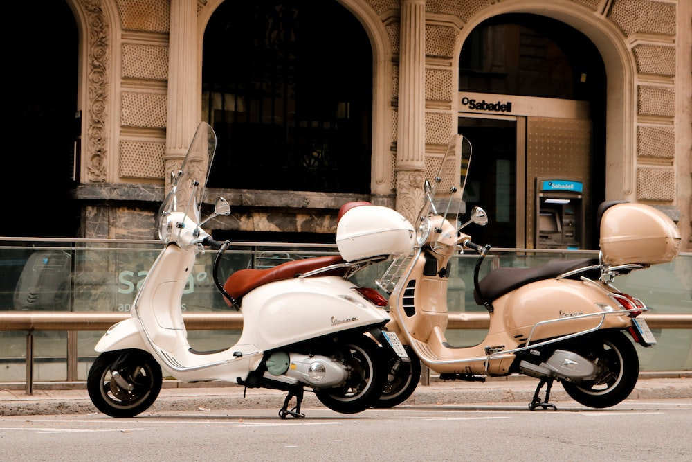 red and white motor scooter parked beside brown concrete building during daytime