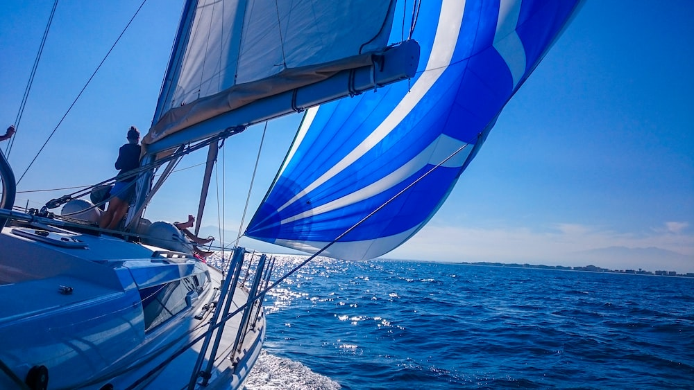 white and blue sail boat on sea during daytime