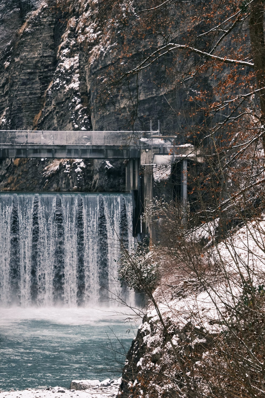 white water falls on gray concrete bridge