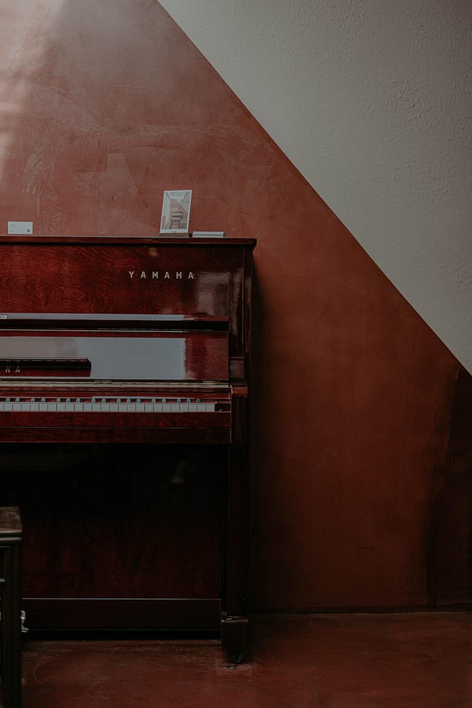brown upright piano near brown wall