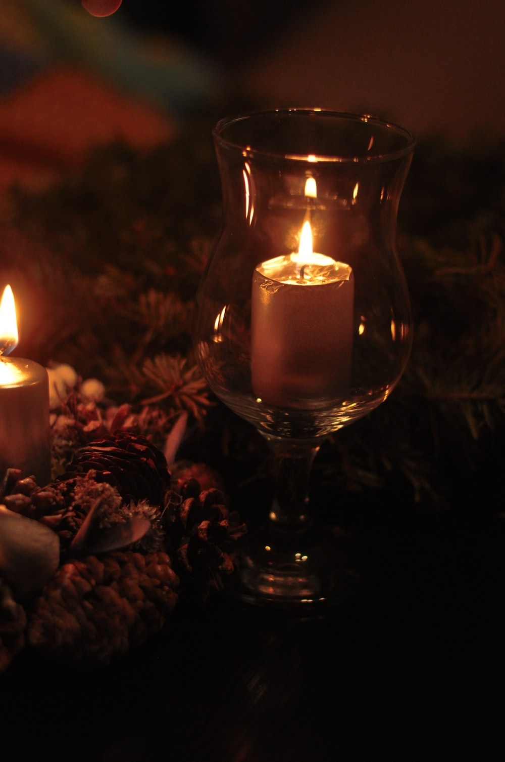 lighted candle in clear glass candle holder