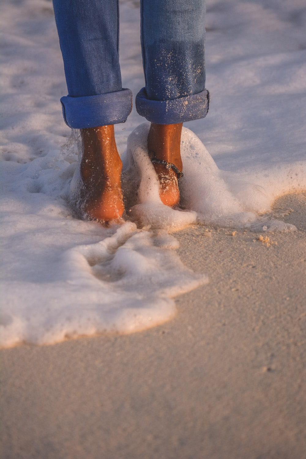 person in blue pants and brown boots standing on snow covered ground
