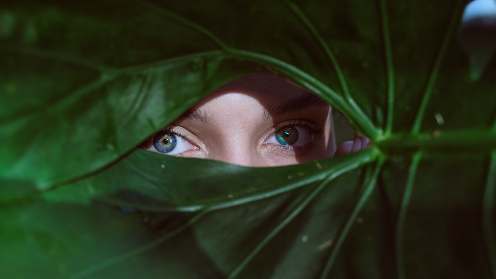 woman in green hijab covering her face with green textile
