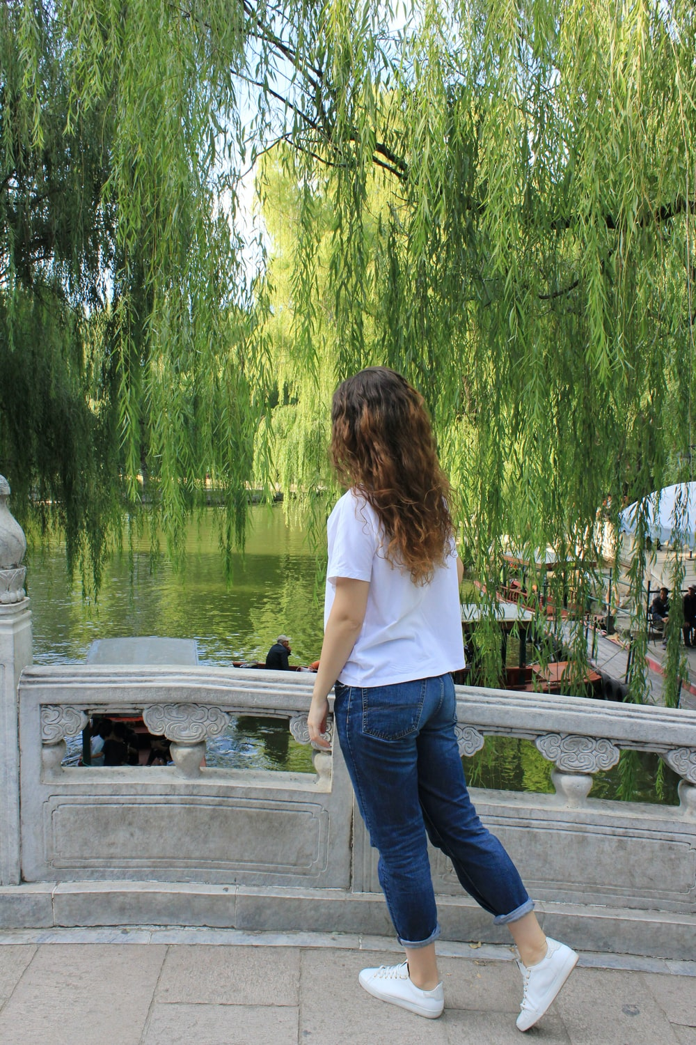 woman in white t-shirt and blue denim jeans standing on gray concrete dock during daytime