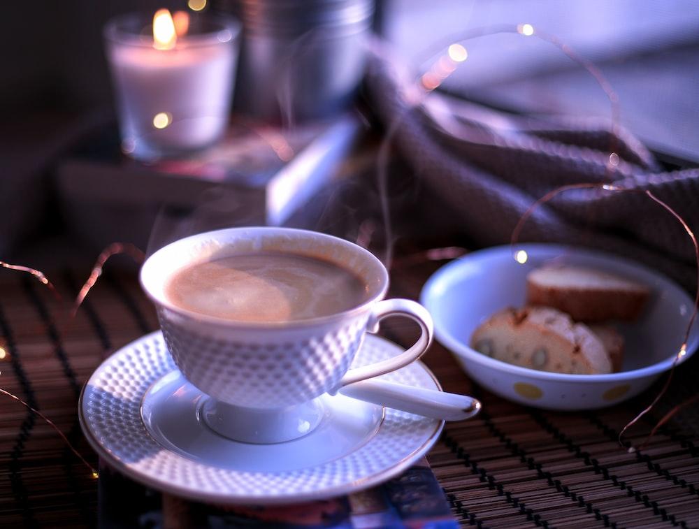 white ceramic teacup on blue saucer