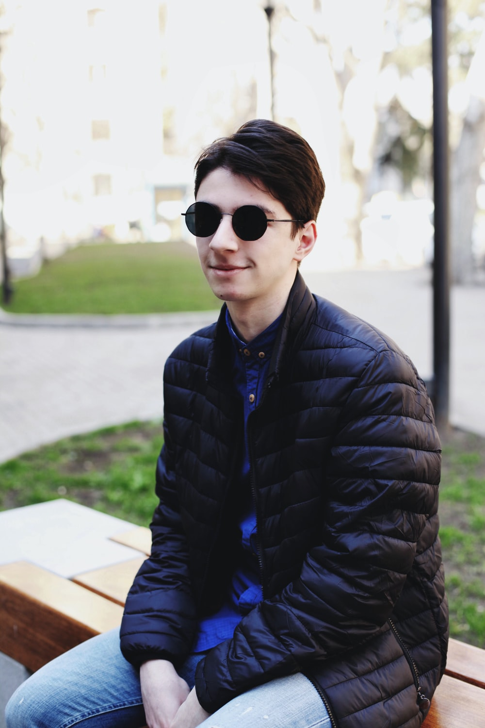 man in black bubble jacket wearing black sunglasses sitting on bench during daytime