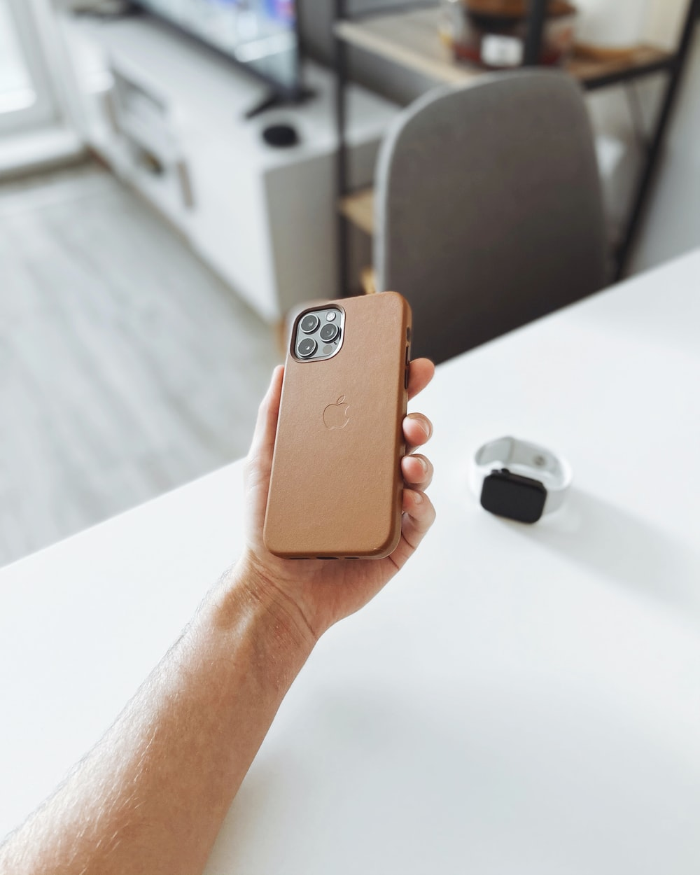 person holding brown iphone case
