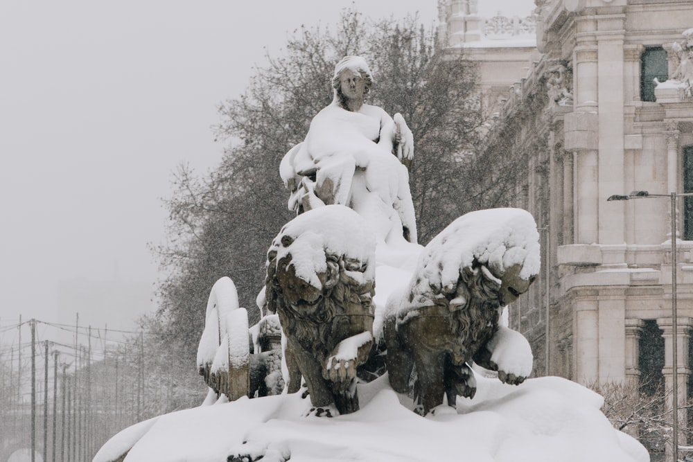 man and woman statue covered with snow
