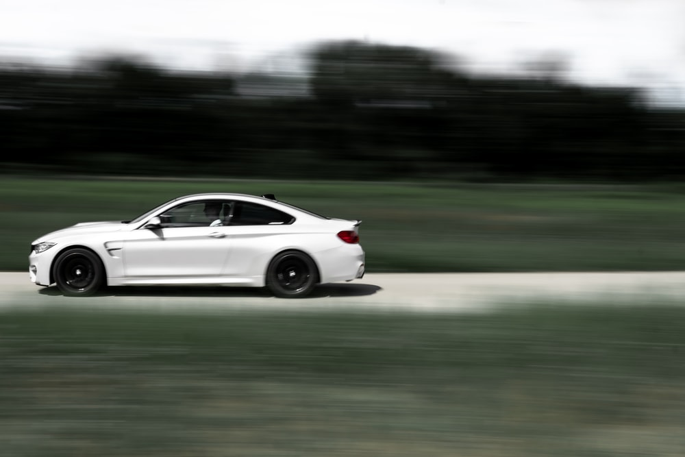white coupe on road during daytime
