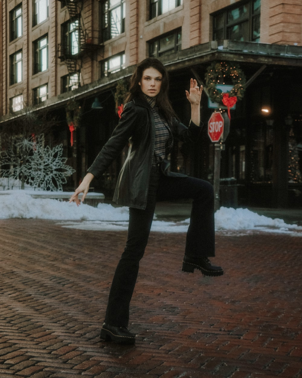 woman in black leather jacket and black pants standing on brown brick floor during daytime
